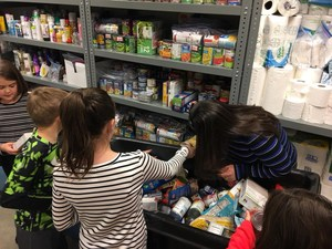 Students stocking food pantry with canned goods
