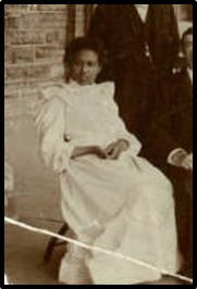 Photo description:  Blanche Wilkins, as a young black woman, sitting; a man standing and one sitting next to her.