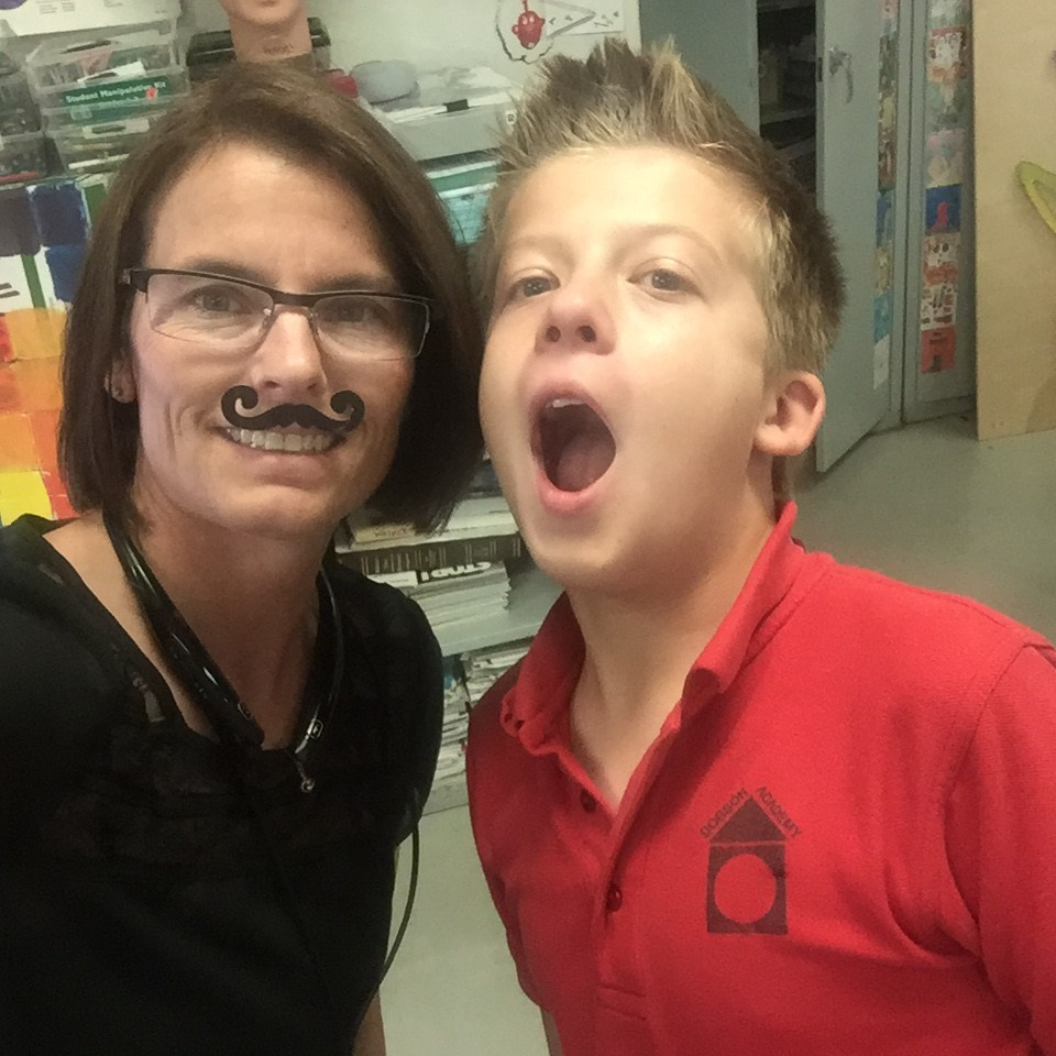 The principal with fake mustache next to a middle school student.