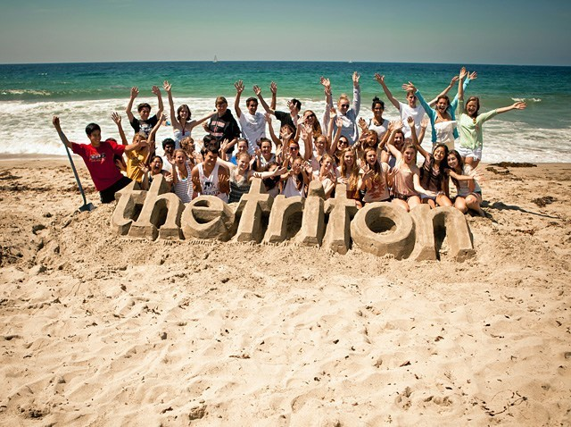 The Triton yearbook staff on the beach with Triton sand sculpture