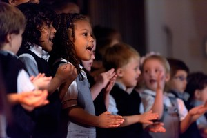 A group of younger students singing and clapping