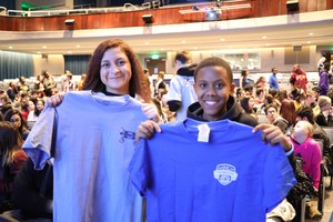 Two students hold up t-shirts from Dorman and Limestone College.