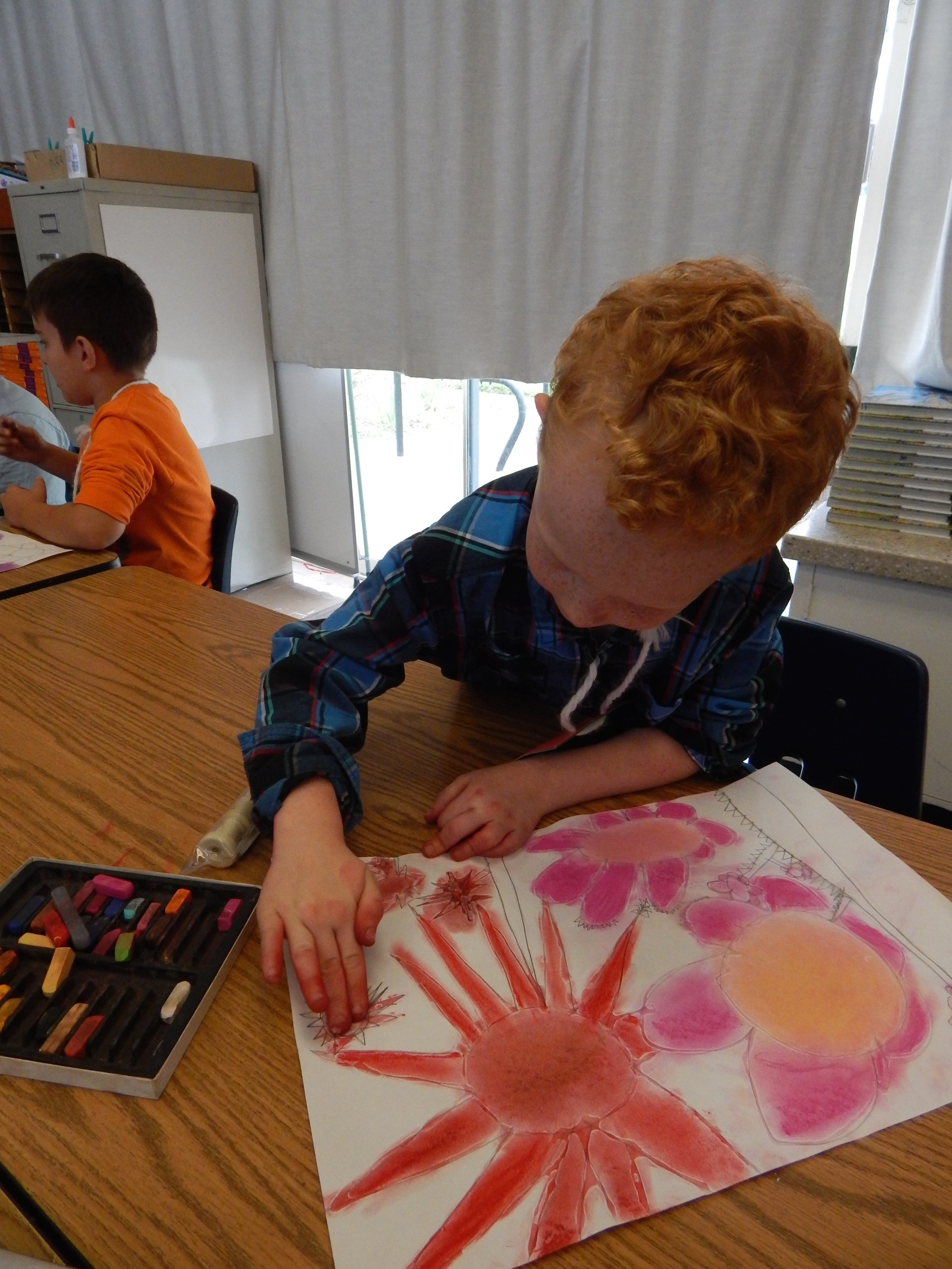 Boy drawing flowers with chalk pastels.