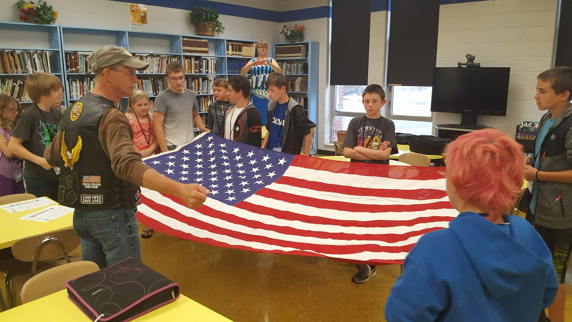 Veterans teaching students how to fold the American flag