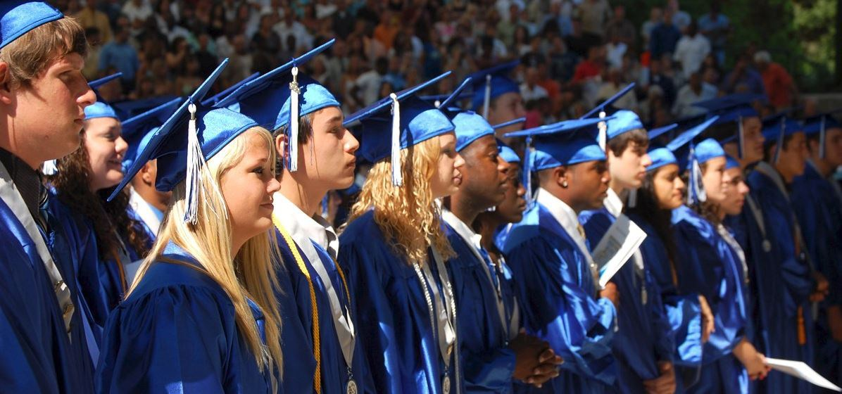 Row of high school graduates in blue cap and gowns