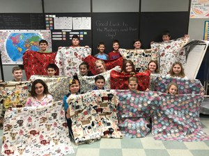 group photo of children holding up patterned blankets