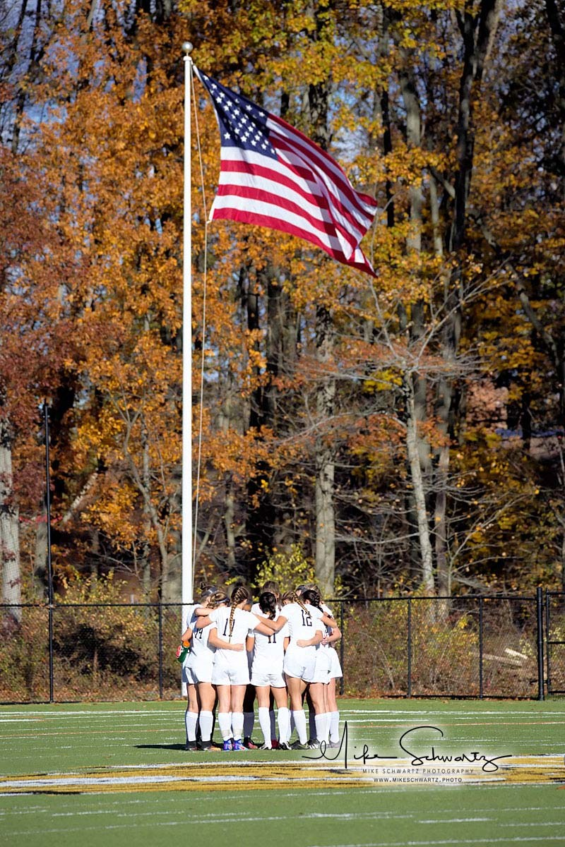 CHS girls soccer team huddles on field with U.S. flag in background
