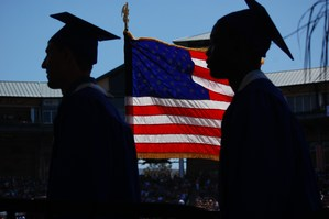 Graduates in sillhouette wth american flag between them