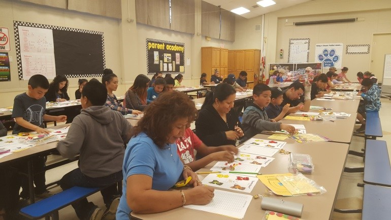 Parents complete an activity at a Parent Academy event.