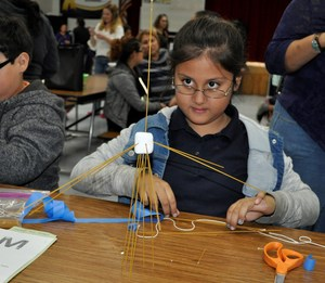 Foster Elementary School third-grader Liliana R. Olivas builds a tower of spaghetti and a marshmallow during the school's first STEAM Night.