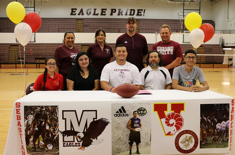 Family and coaches look on as Sebastian signs his letter of intent.
