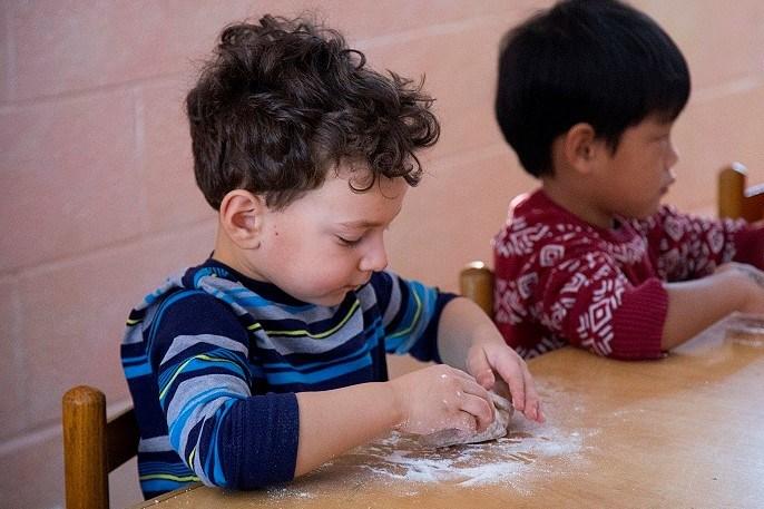 Kindergarten boy kneading dough