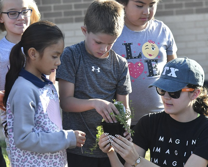 Students planting a flower at Lillian Elementary School.