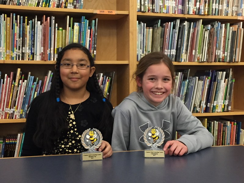 two girls sit in library with their awards