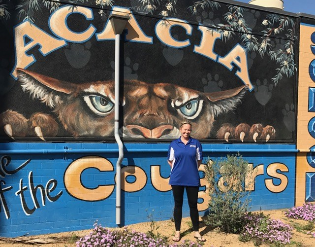 Anne Rogers in front of an Acacia Middle School sign.