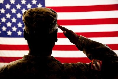 Veterans Day Ad, Man Saluting, American Flag. Red, White and Blue