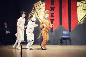 Three students walking on a stage dressed up