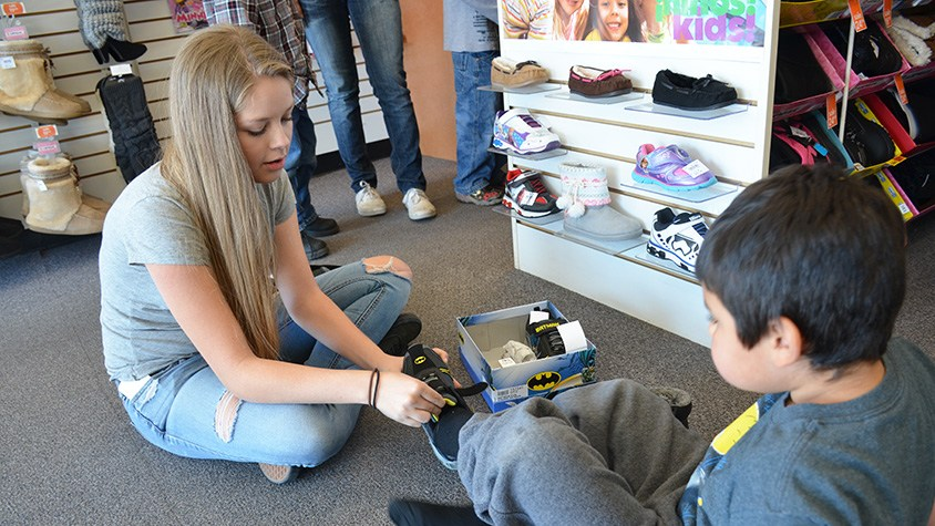 Upper School volunteer student helping child try on shoes