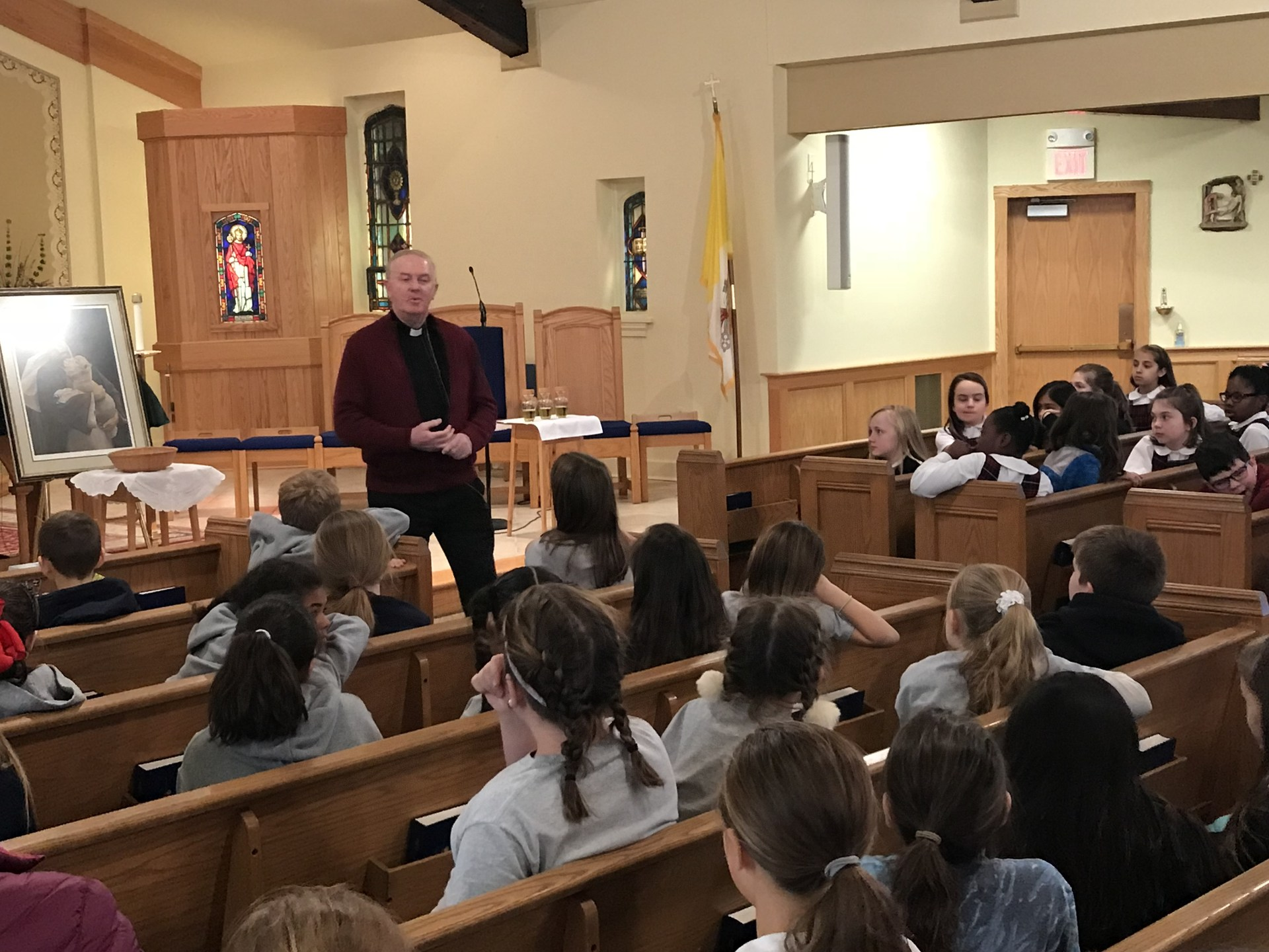 Priest talking about Jesus to fourth-grade students during retreat