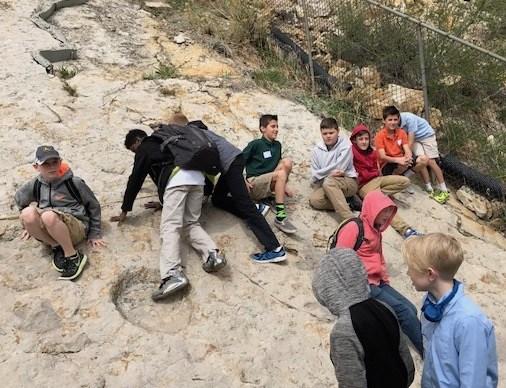 student climb on dinosaur footprints at Dino Ridge on field trip