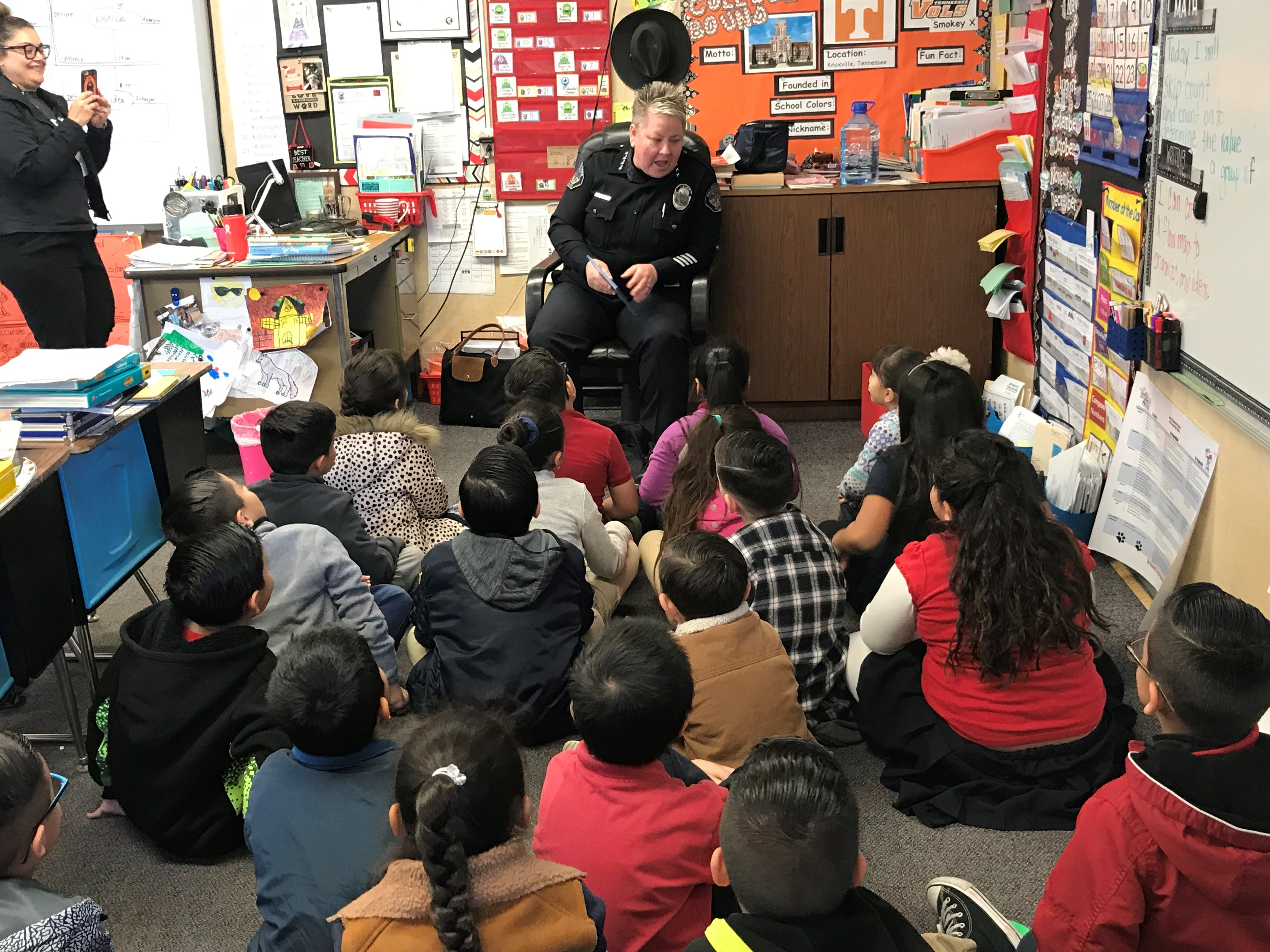classroom of students being read to by an officer