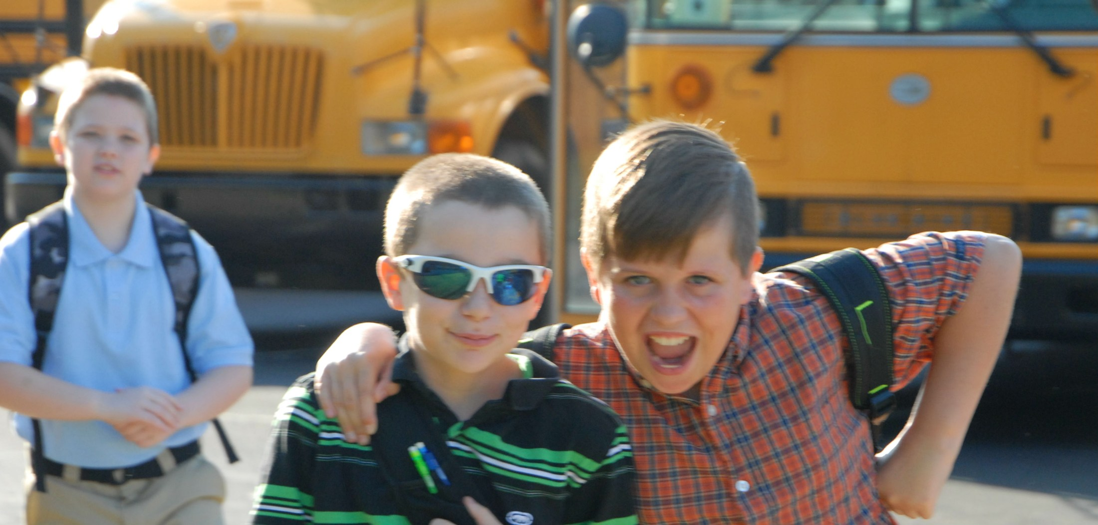 two boys posing in front of buses