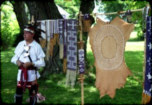 Adult in traditional Native American clothing and headdress stands in front of clothes line with multicolored blankets