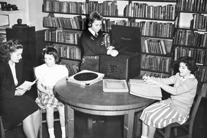 Three children reading or listening to a talking book