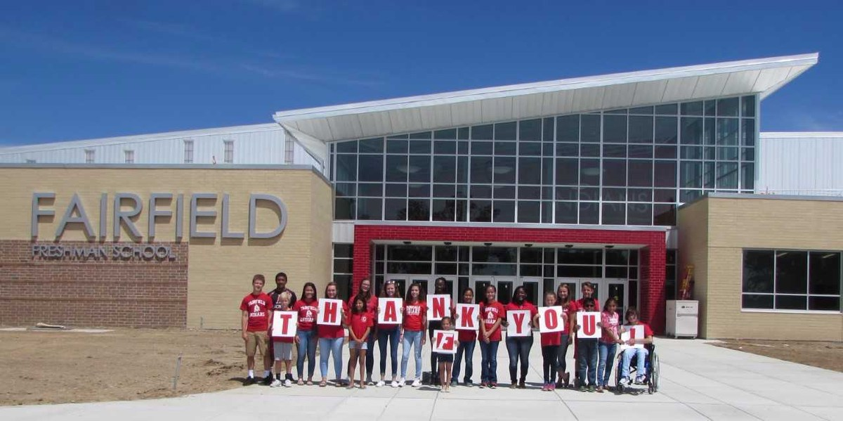 "Fairfield students standing in front of the new Freshman School Building. THey are holding letters that spell out "" THANK YOU!"" This is to thank the community for their support in getting three new schools."