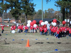 A group of students with red t-shirts out on the field.