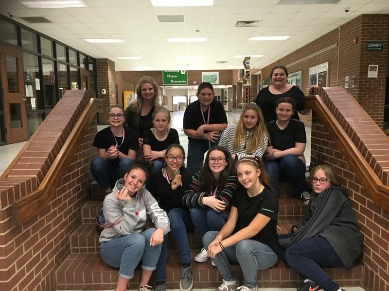One act play students and sponsors with their trophy siting on steps.