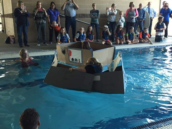 Student floating in pool in a cardboard boat
