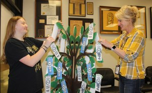 CHS student and Principal putting donation tags on Prom Tree for Ingleside HS Prom project