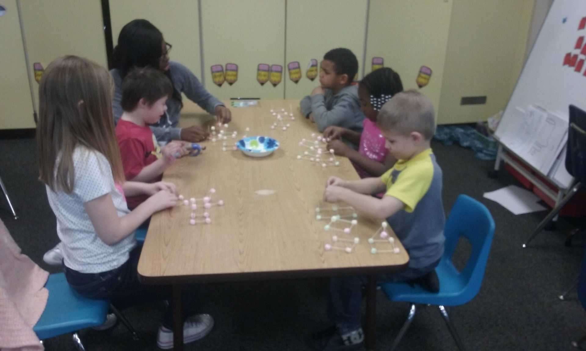 A table of students build shapes with marshmallows and toothpicks