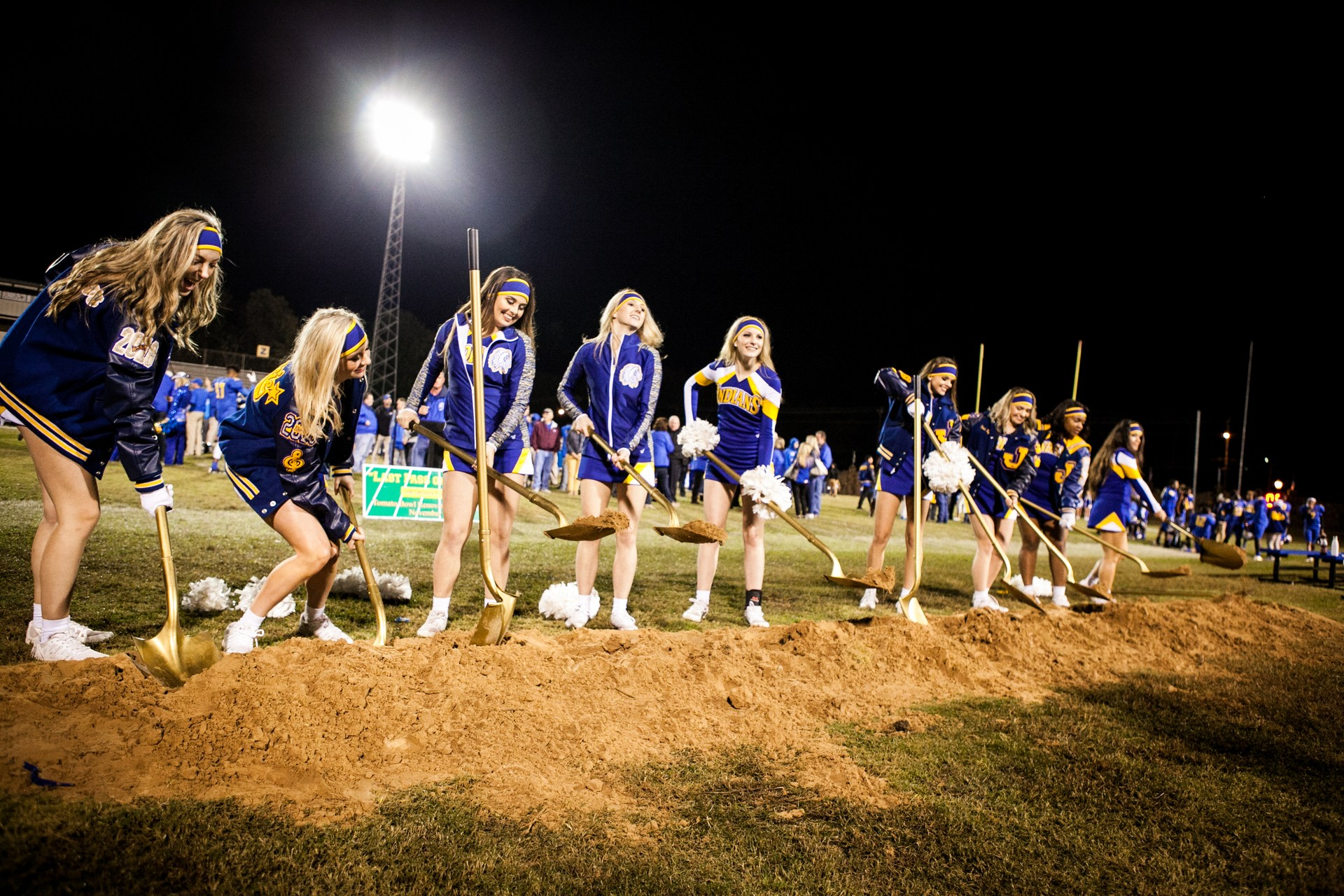 Cheerleaders on the field breaking ground