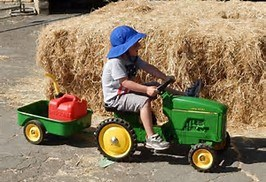CHILD ON SMALL TRACTOR WITH WAGON