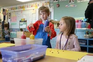 Preschool student pretends to be an art teacher.