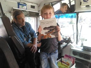 Picture of a student on a bus with the driver, showcasing a book on board
