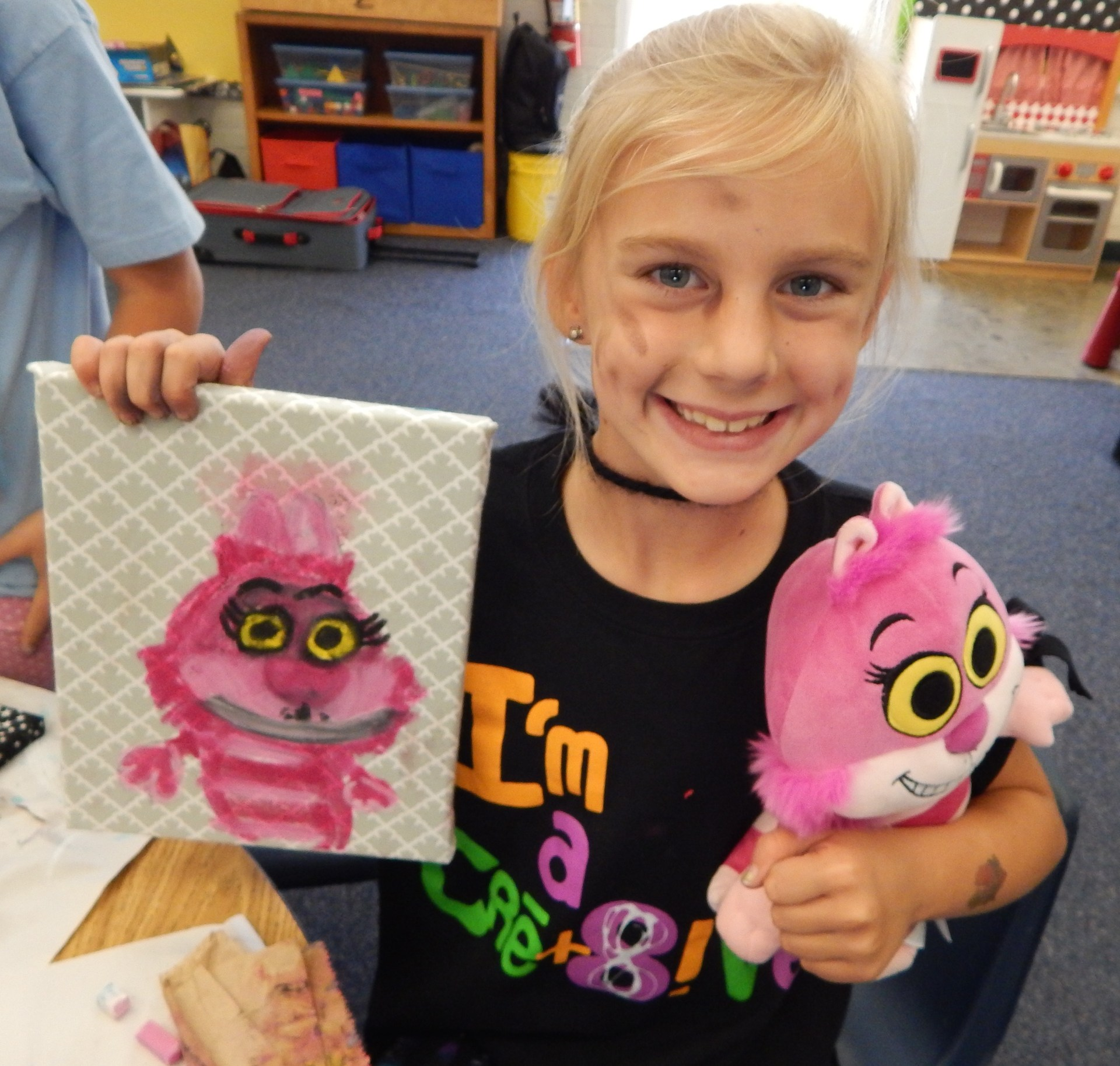 A girl showing her oil pastel drawing of a stuffed animal cat.