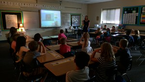 Students watch a story-telling video of the book September Roses on the 9/11 anniversary.
