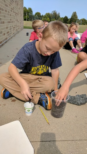 Rayne Sutton adds soil to his cup to plant his sunflower seed.