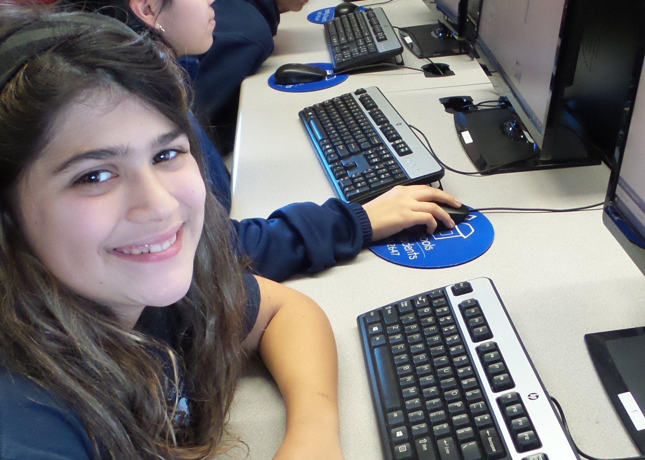 Student on computer smiling.