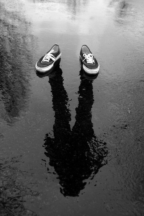 Black and white photo of legs and their shadow.