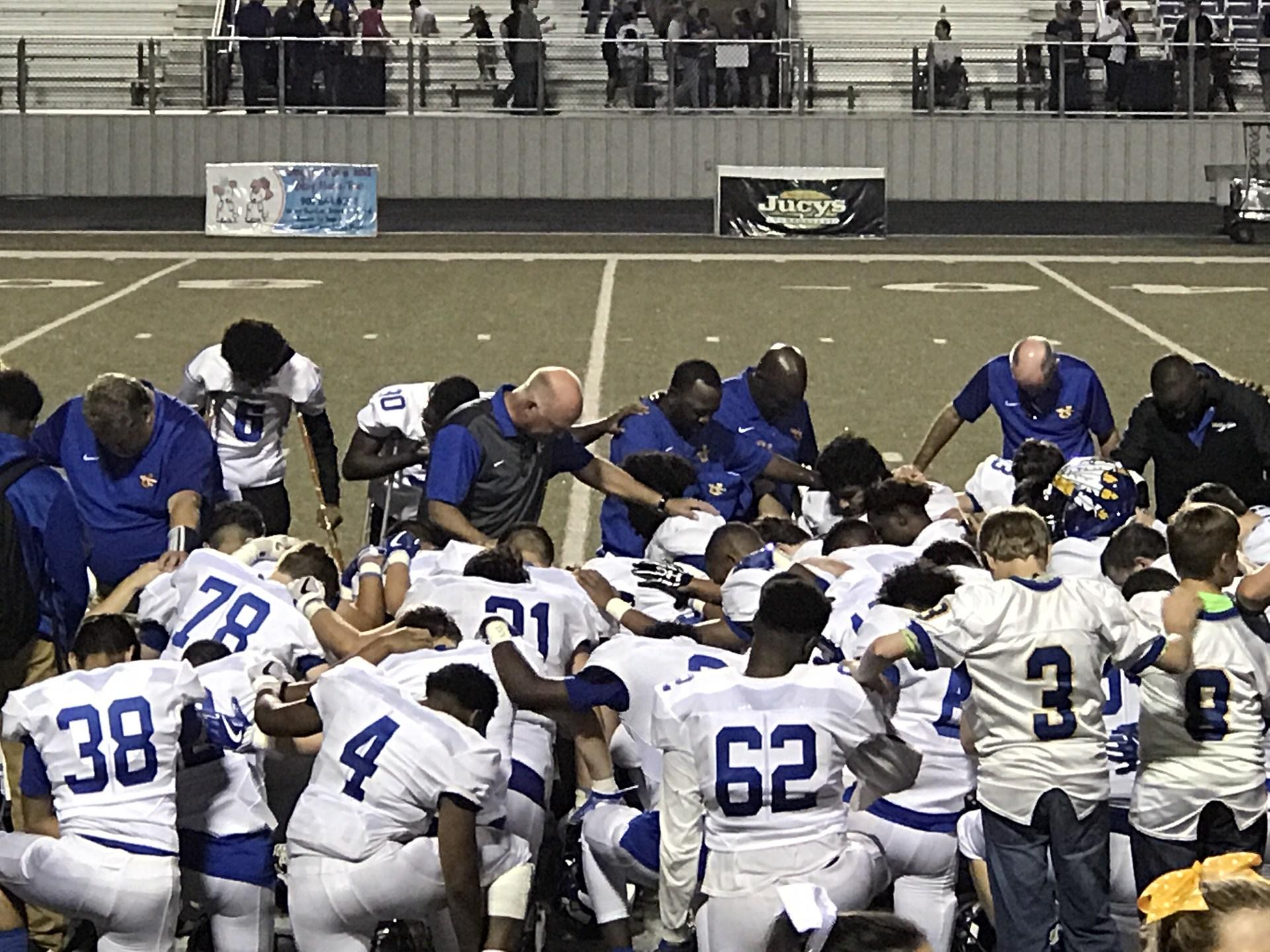 team praying after game