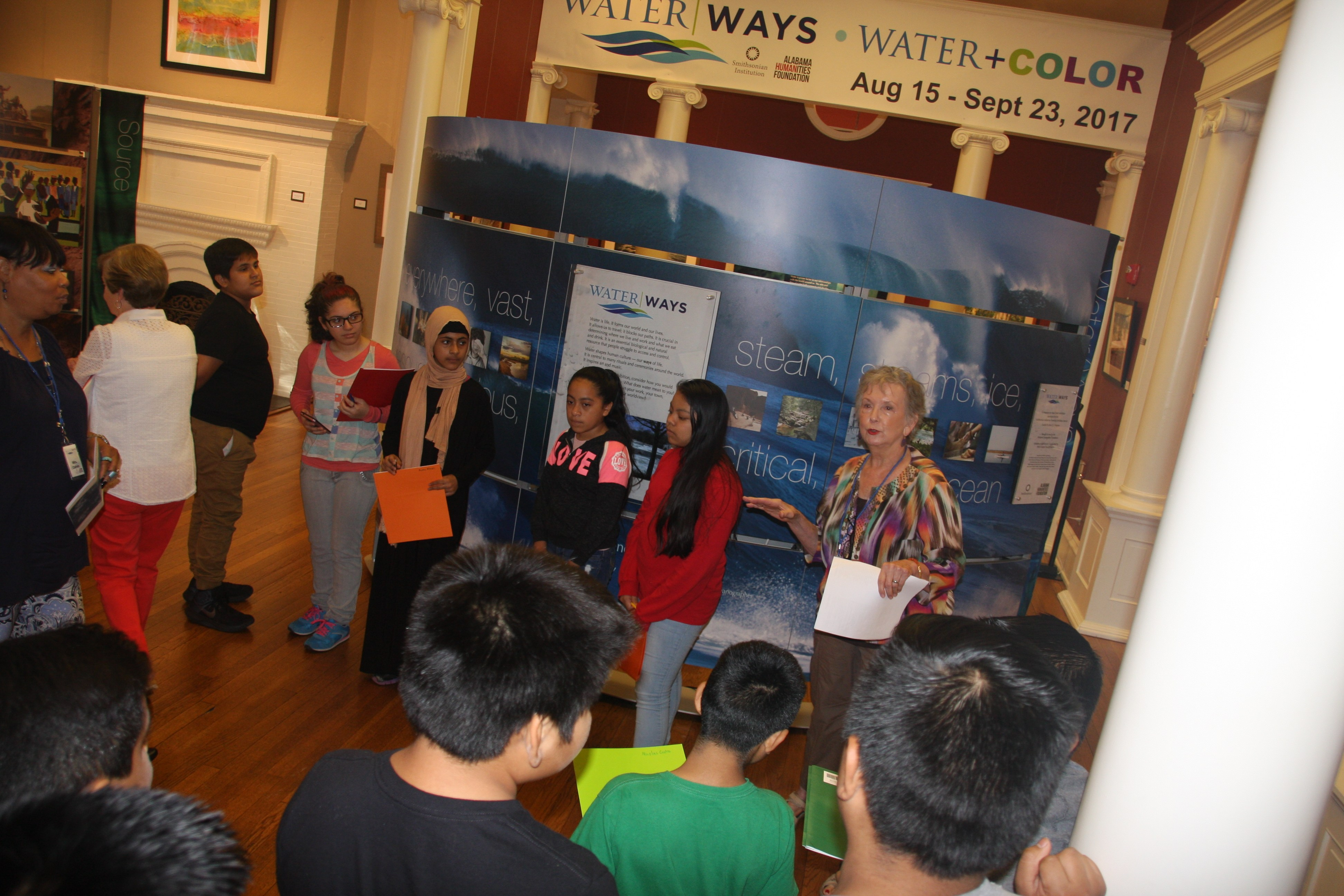 Seventh graders attentively listen to the docent explain one of the kiosks of the exhibit.