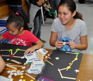 Jones Junior High student Lysandra Arce joins her sister, Foster first-grader Kaylinn, at the school's first STEAM Night. Here, she recreates the Perseus constellation.