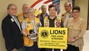 Group picture of Lions Club members with the district head nurse holding a small sign about the vision screening