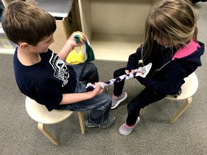 Two students concentrate as they work together to braid the t-shirt strips into toys.