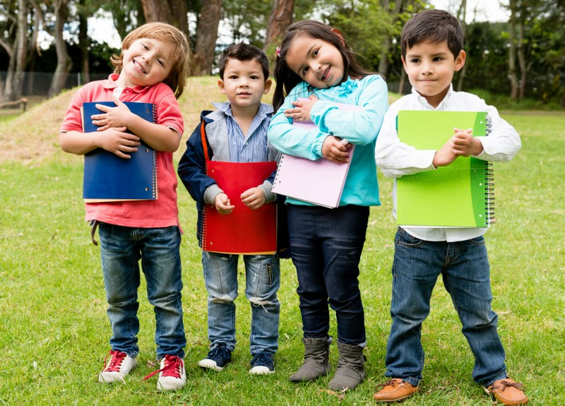preschool kids holding notebook outside in grass