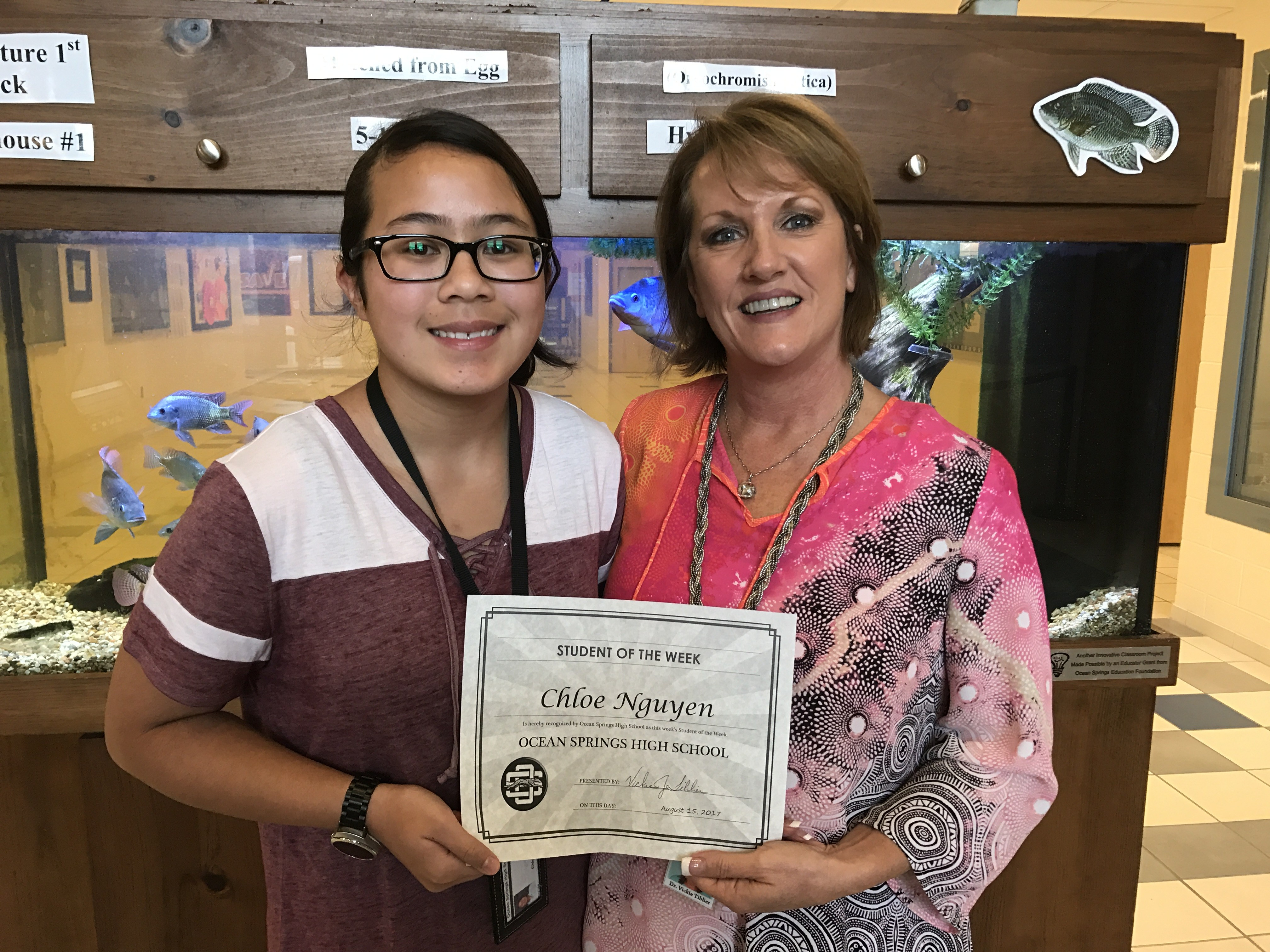 Student of the Week Chloe Nguyen receives a certificate from Dr. Tiblier.
